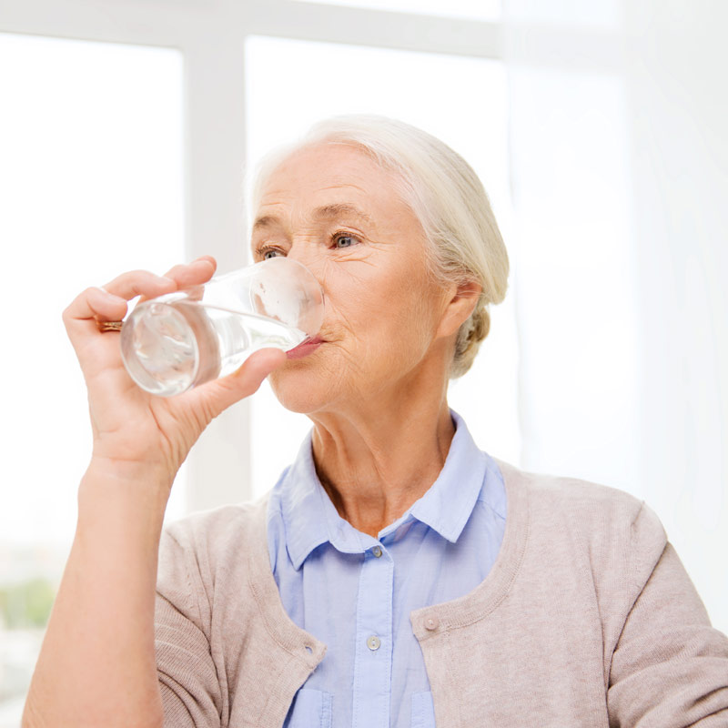 Older lady drinking a glass of water