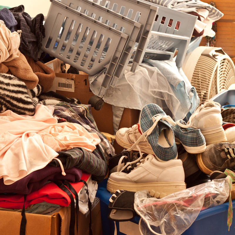 Messy pile of hoarded belongings including clothing shoes and a fan